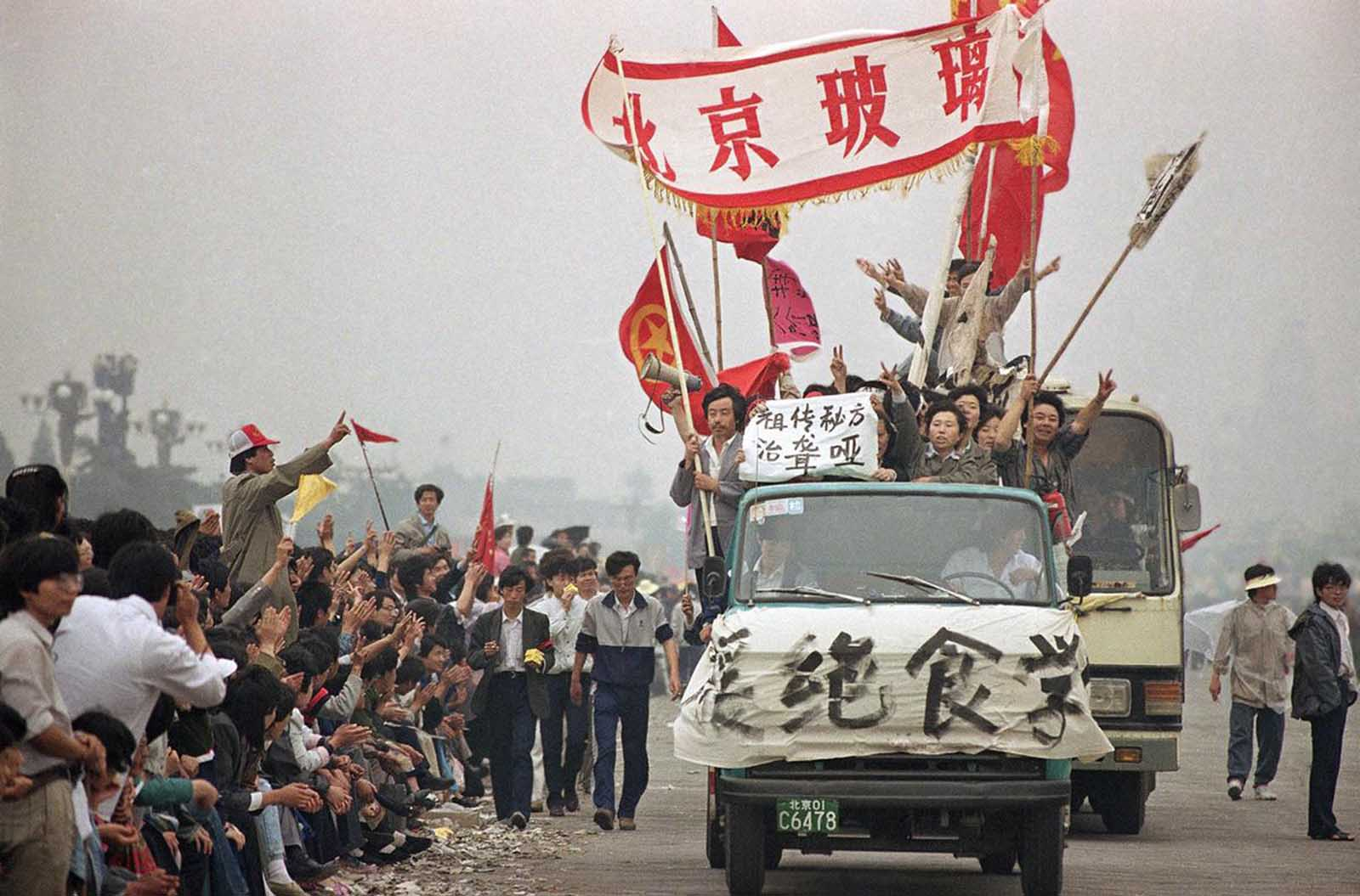 Enthusiastic demonstrators are cheered by bystanders as they arrive at Tiananmen Square to show support for the student hunger strike, on May 18, 1989.