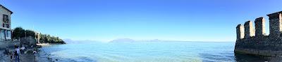 Panoramabilde av sjøen flankert av land til venstre og en borgmur til høyre.