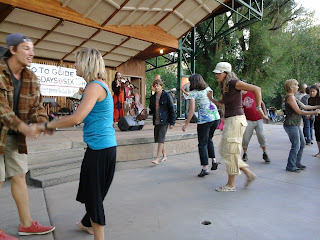 People dancing to the live music along the river park.