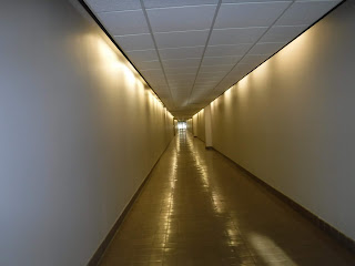 white walls and white ceiling tiles line a long hallway in the Sioux City Skywalk without windows or decoration