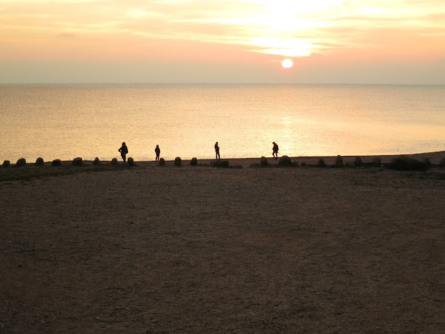 Four photographers along edge of sea at sunset having taken their pictures.