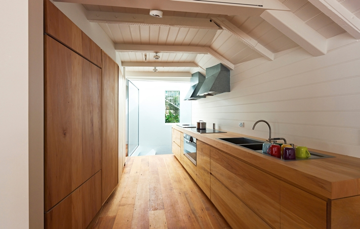Kitchen with wooden furniture in Lavender Bay Boatshed by Stephen Collier Architects