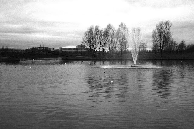 Black and white picture of the fountain and a wooden bridge.