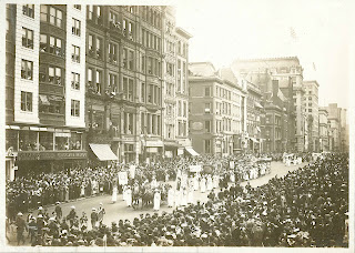 A black and white photograph of a parade moving through a crowded street.