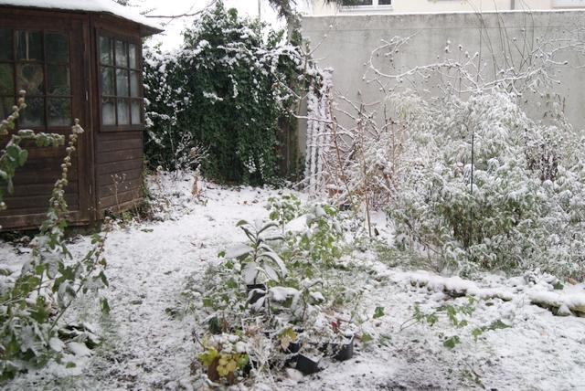 Gartenhäuschen und Beete mit Schnee bedeckt