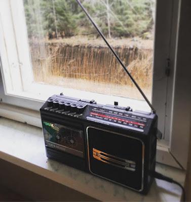musta vanha radio ja kasettisoitin  ikkunalaudalla ikkunasta näkyy joki