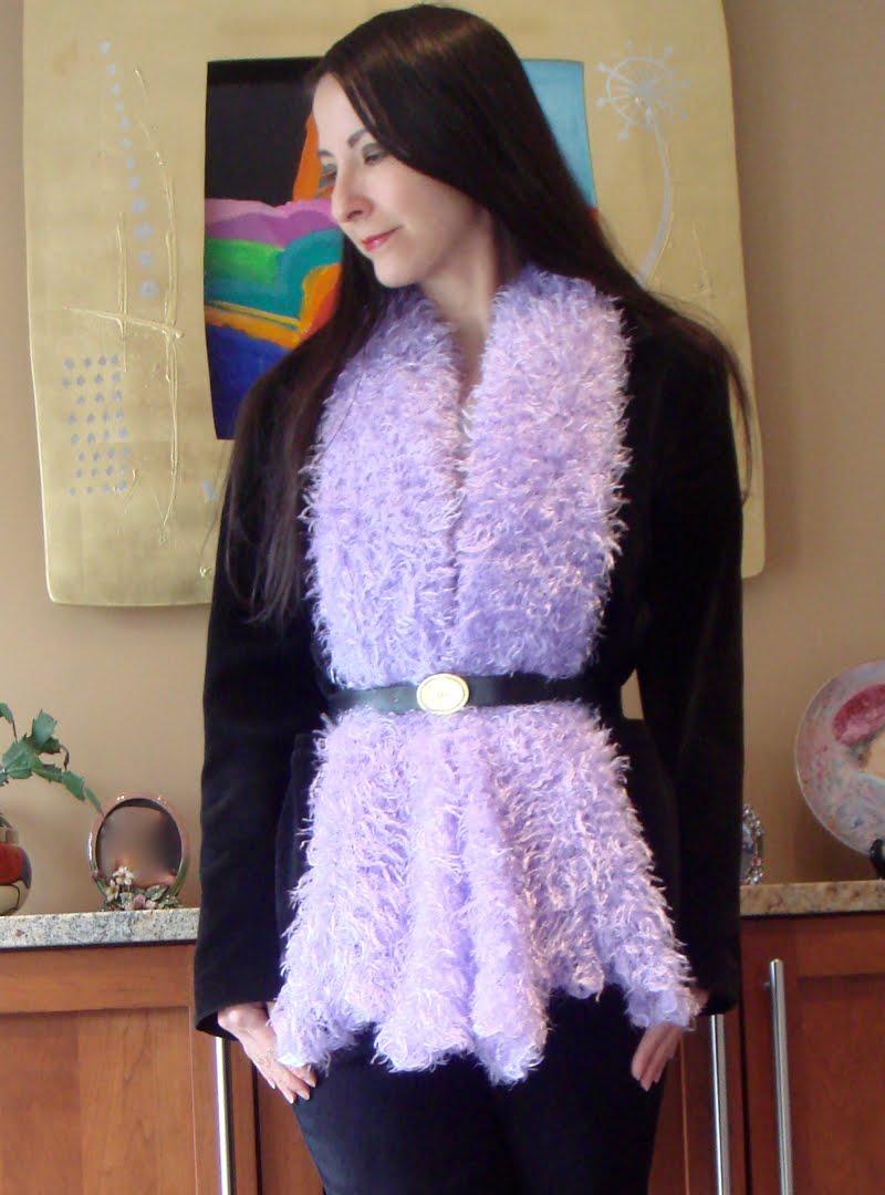 Wearing black velvet blazer, handmade purple fuzz scarf, belted over the blazer.