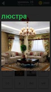 В комнате с двумя окнами на потолке висит великолепная люстра над столом