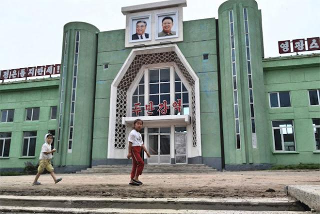"""Khi quay trở lại nhà ga, Chu thấy hai bức chân dung của lãnh tụ Triều Tiên Kim Nhật Thành và nhà cố lãnh đạo nước này Kim Jong Il cùng dòng chữ """"sống mãi"""" bên dưới."""