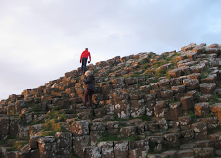 Two people climbing up the tiers of basalt columns, Giant's Causeway, Northern Ireland