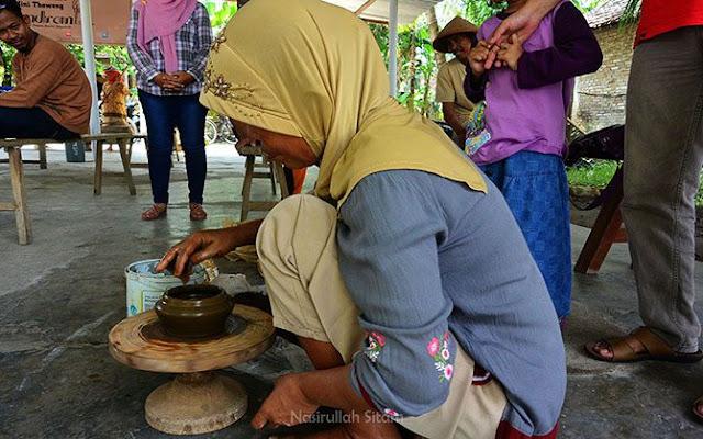 Seorang ibu membuat pot dari gumpalan tanah