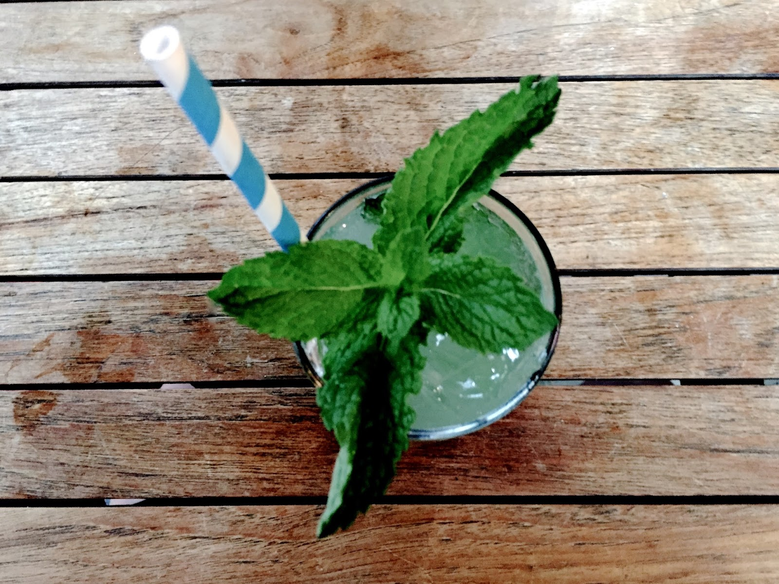 cocktail with mint and blue & white striped straw