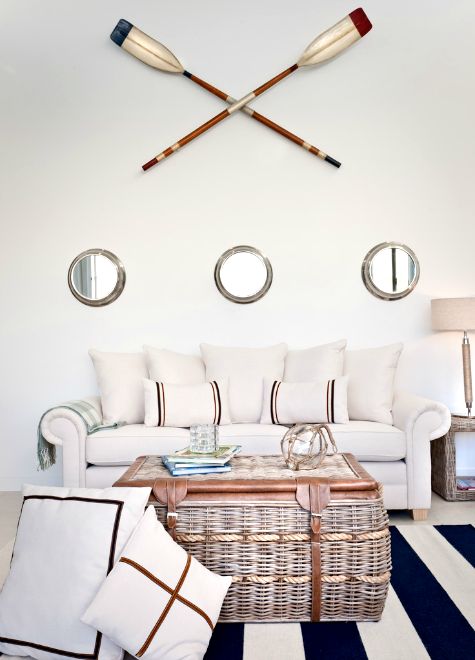 porthole mirrors in living room above sofa