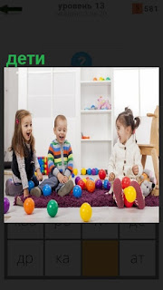 На полу в комнате играют несколько детей, вокруг игрушки