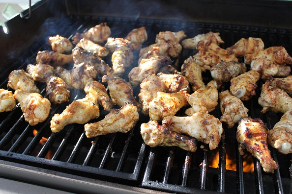 this are chicken wings cooking on the grill with a hot fire that have been marinated and seasoned now cooking