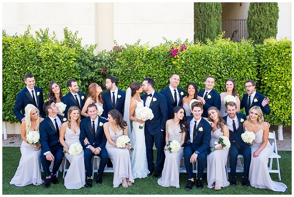 large wedding party in navy suits and mauve blush dresses with white rose wedding bouquets