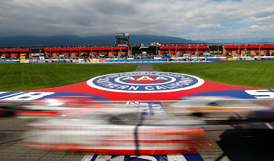 Blurred image of Nascar race cars passing the start/finish line at over 200mph with AAA logo in background on the infield