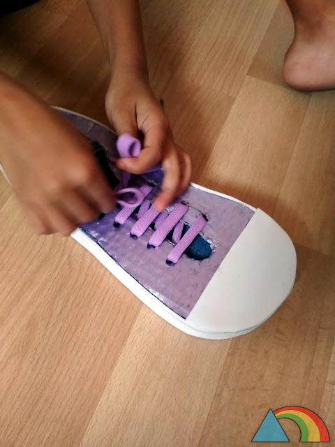 Niño practicando atarse los cordones con un zapato de cartón DIY