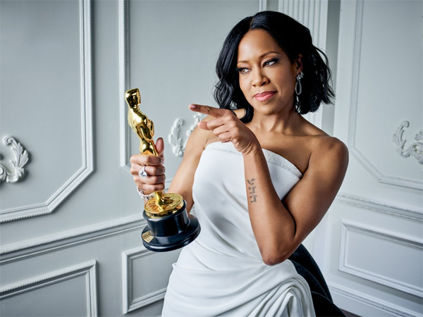 image of Regina King in a white gown, holding up her Oscar backstage after her win