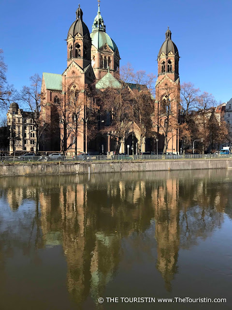 Red brick church under a blue sky with its reflection in a river