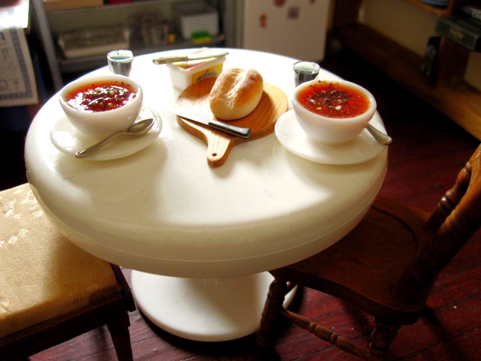 Dolls house miniature table set with two bowls of soup and glasses of wine, and a loaf of crusty bread