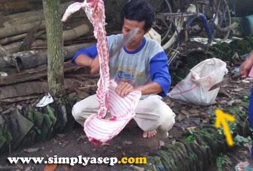 TAJAM :  Bisa dibayangkan betapa tajamnya pisau atau belati yang dipegang agus mampu memotong tulang belulang kambing.  Karung dibelakangnya adalah tempat kulit sang kambing (lihat anak panah-red)  Foto Asep Haryono