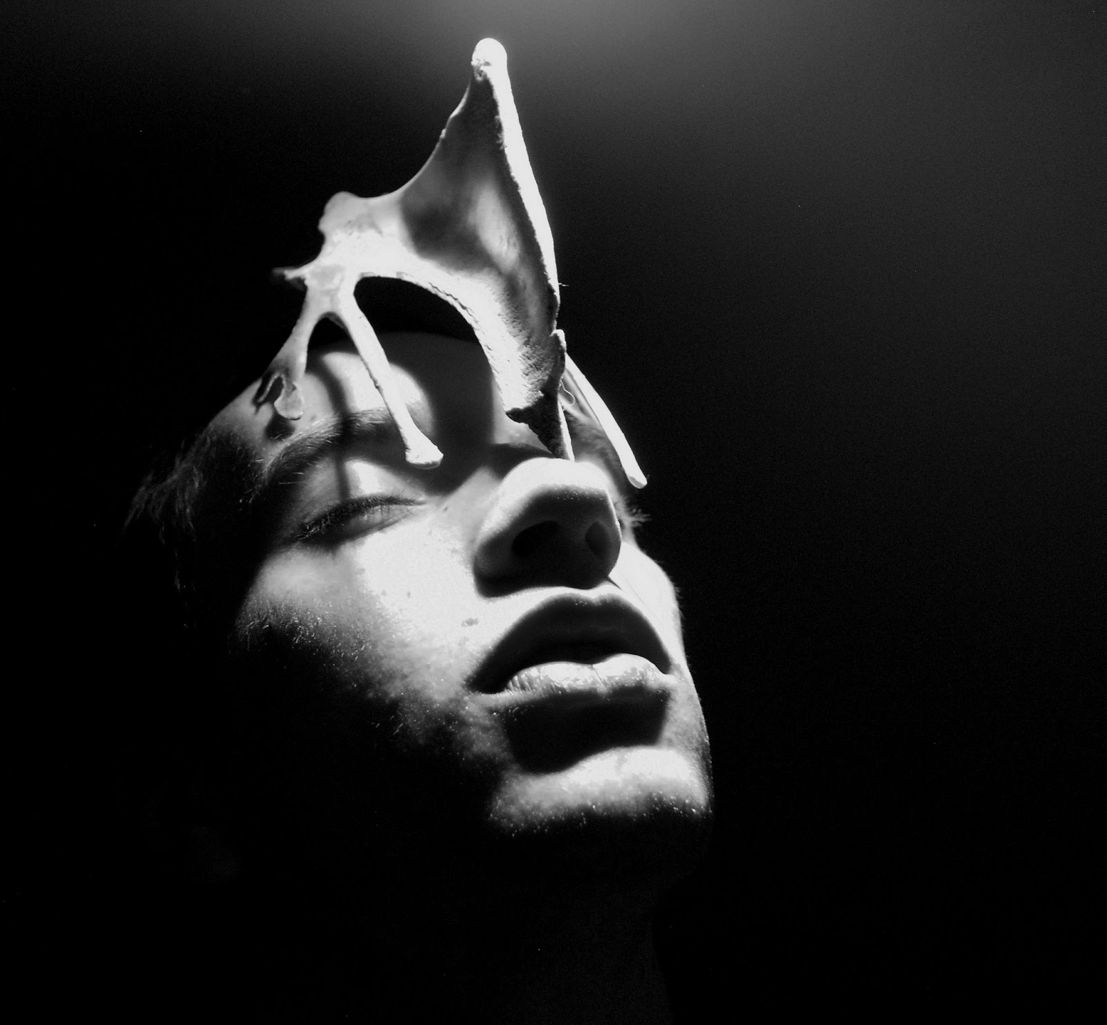 I created the strong contrasted look by placing the models head very near to direct light i felt that the mood of the photographs suited black and white
