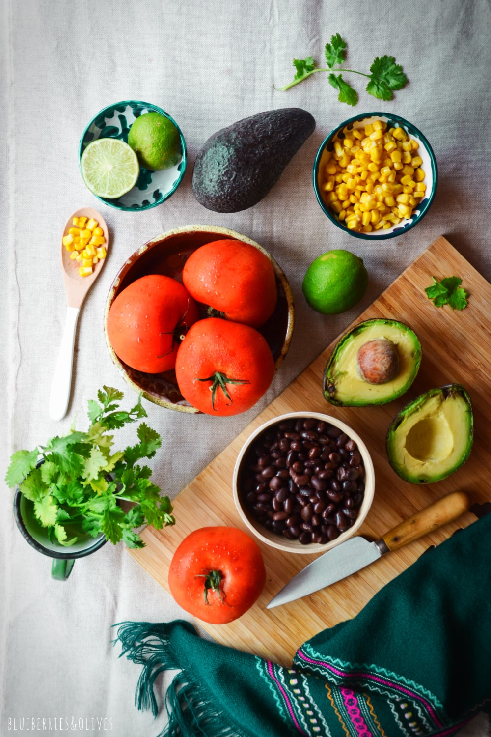 INGREDIENTS STUFFED TOMATOES, WOOD CUTTING BOARD WITH KNIFE, CORN, AVOCADO, LIME WEDGES, CILANTRO LEAVES, BLACK BEANS