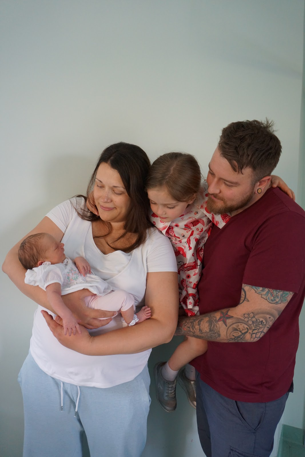 mum, dad and sister looking at a newborn