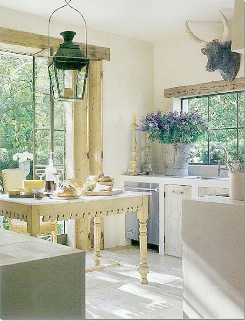 Pamela Pierce's #Frenchfarmhouse #FrenchCountry rustic elegant kitchen with ox head, lantern, and antique French pastry table on Hello Lovely Studio