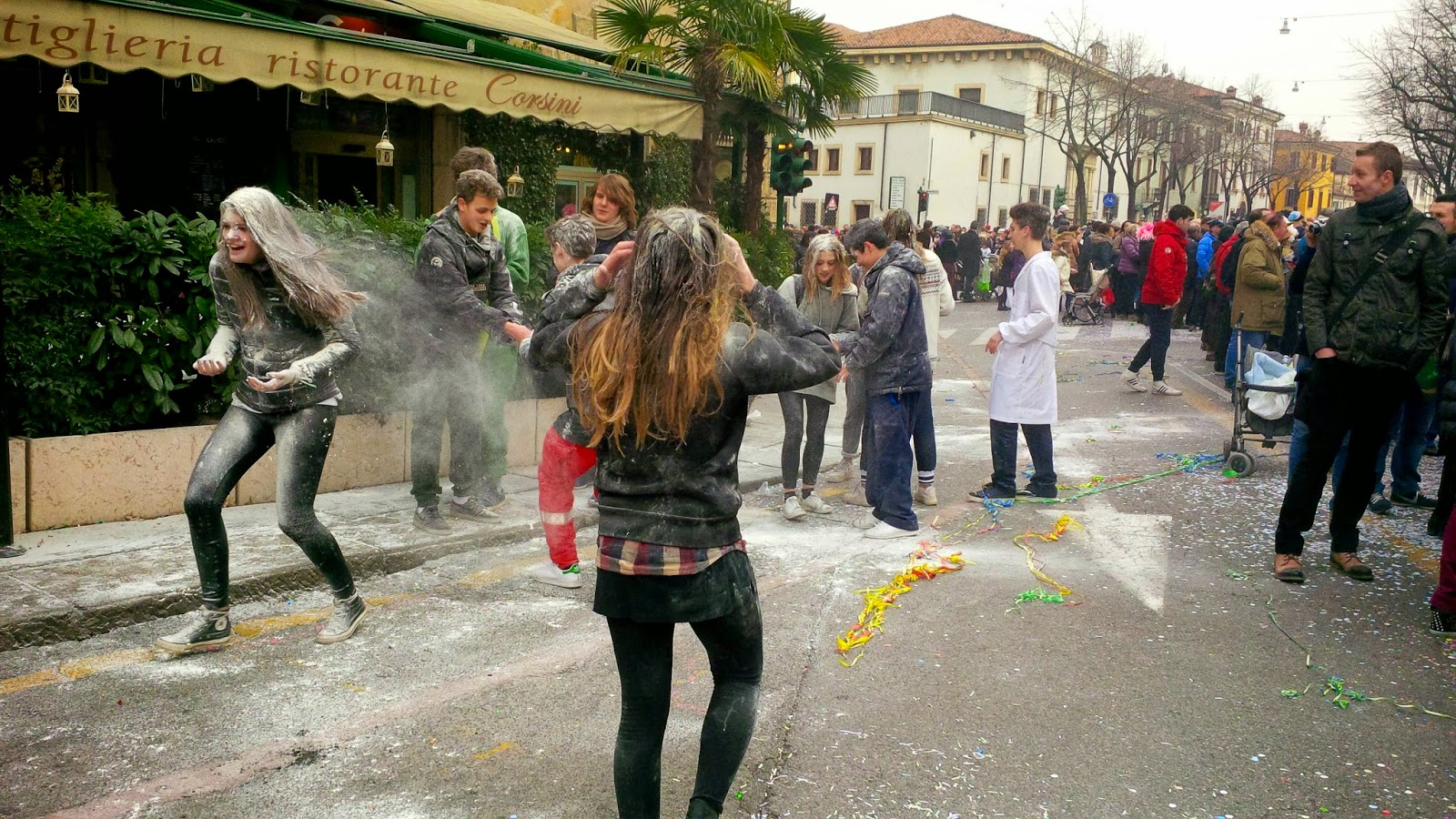 Teenagers throwing flour at each other during the parade for Verona Carnival