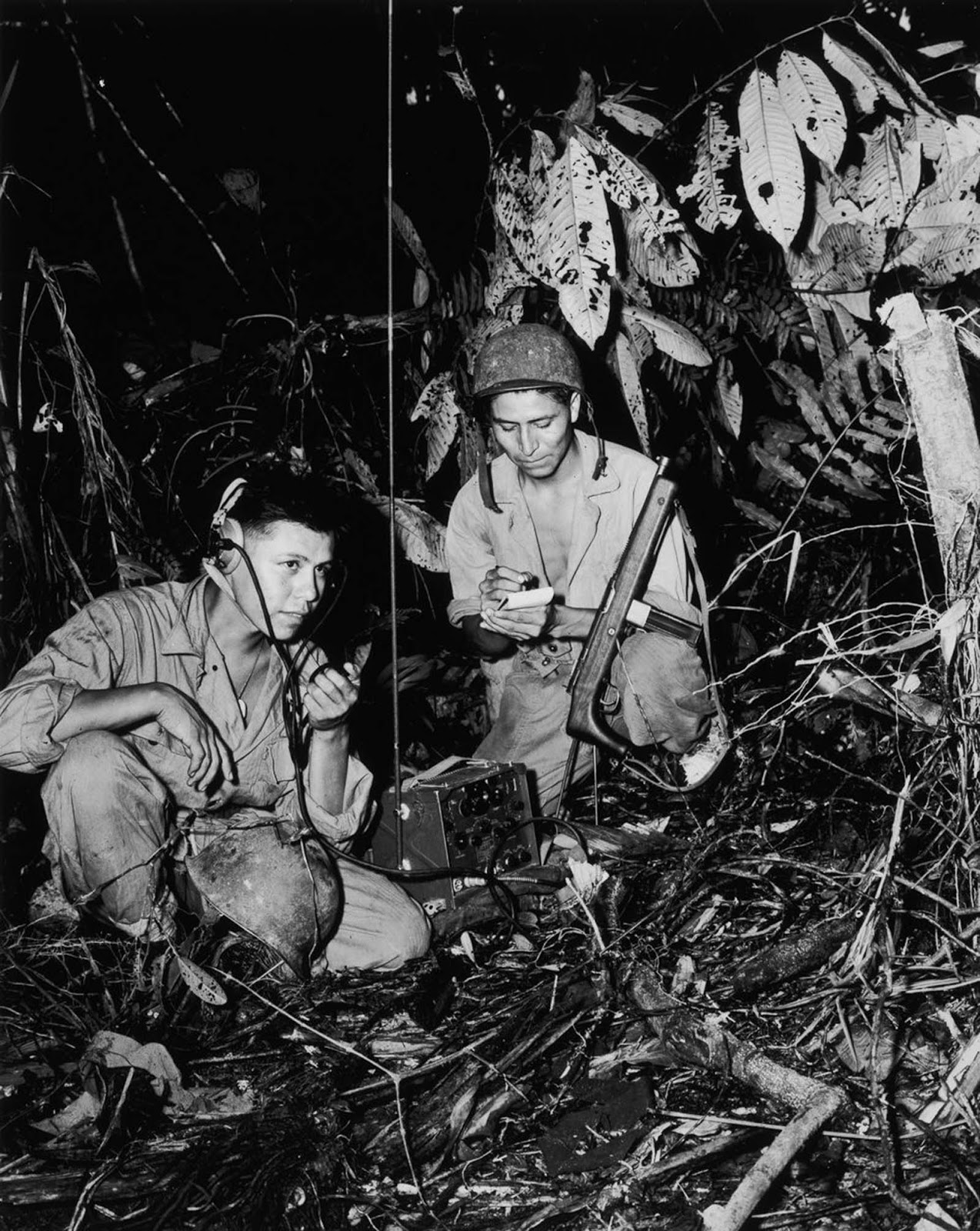 Navajo code talkers Cpl. Henry Bake, Jr. and PFC George H. Kirk transmit messages during combat on Bougainville. 1943.