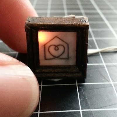 Tiny one-twelfth scale framed sketch of a heart in a house, with a light behind the sketch.