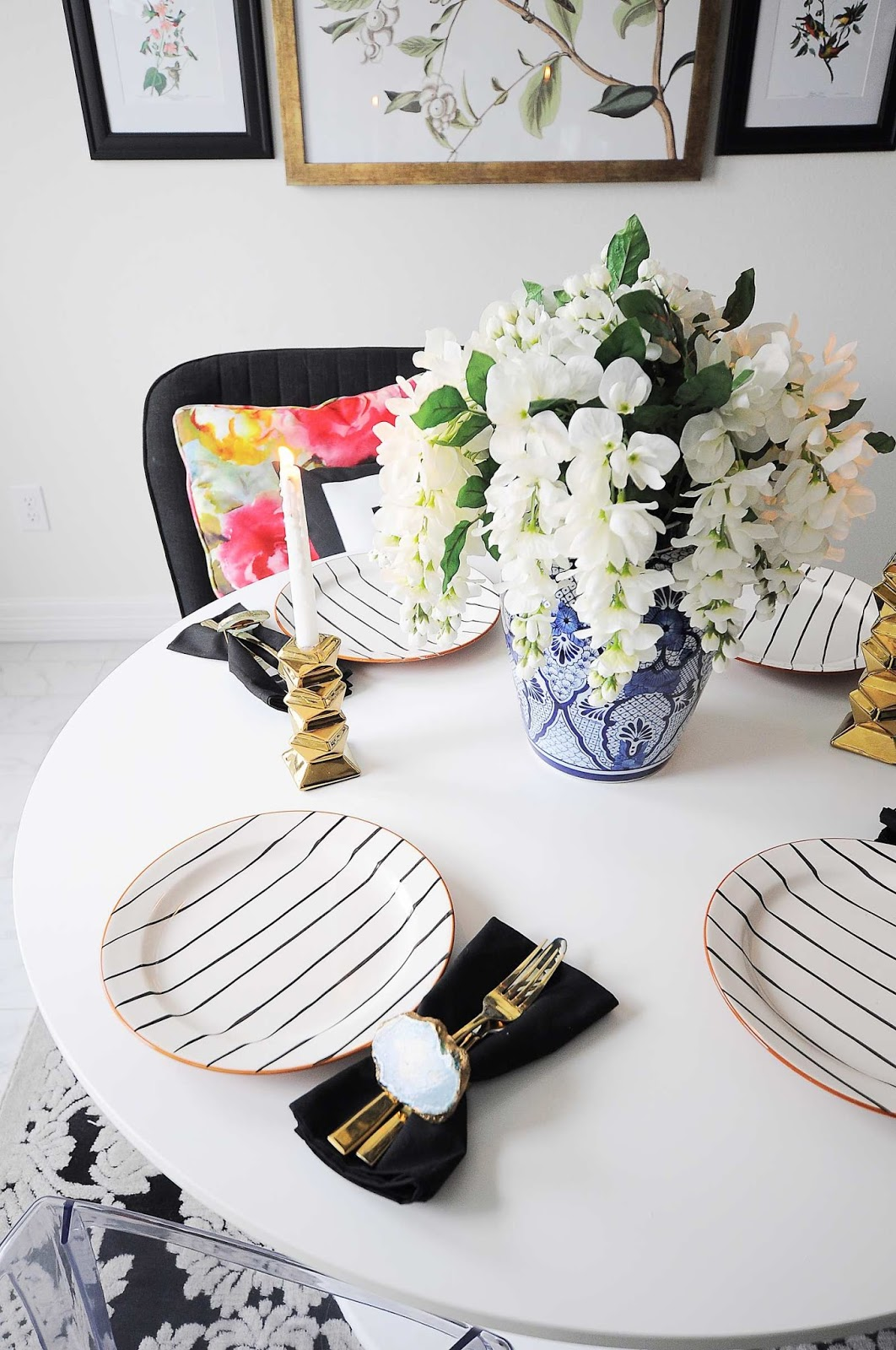 A small dining room gets a $100 makeover using black, white, gold and floral decor.