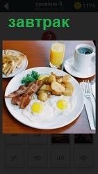 На тарелке утренний завтрак из глазуньи, мяса и картошки. Рядом положены вилка и ножик, стоит чашка с кофе