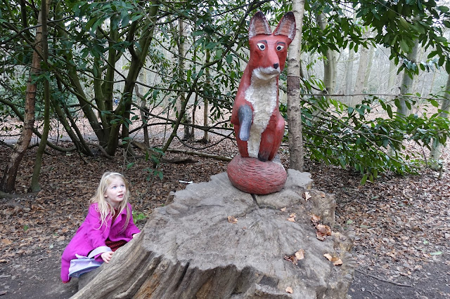 A girl in pink hiding behind a tree stump looking up at a wooden carved fox