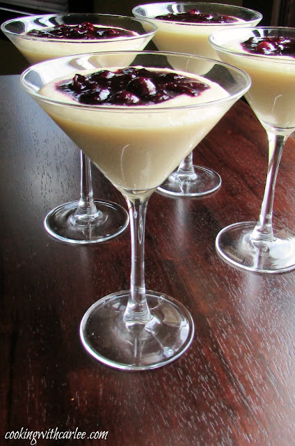 martini glasses filled with cornmeal budino (pudding) and topped with a blueberry marmellata sauce