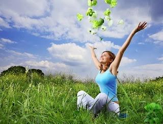 Eine glückliche junge Frau, die am Boden in der Wiese sitzt