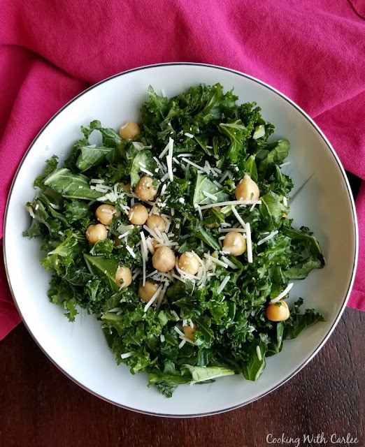 bowl of kale salad with chickpeas and grated Parmesan cheese on top