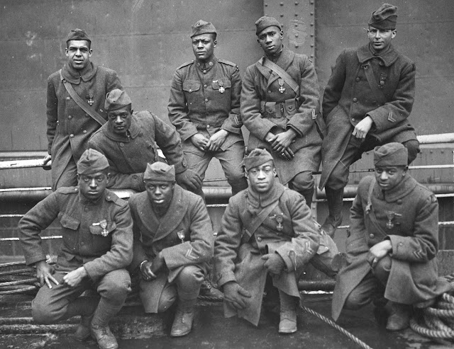 Original caption: Some of the colored men of the 369th (15th, NY) who won the Croix de Guerre for gallantry in action. Front row, left-to-right: Private Eagle Eye, Ed Williams; Lamp Light, Herbert Taylor; Private Leon Fraitor; Private Kid Hawk, Ralph Hawkins. Back row, left-to-right: Sgt. H.D. Prinas; Sgt. Dan Storms, Private Kid Woney, Joe Williams; Private