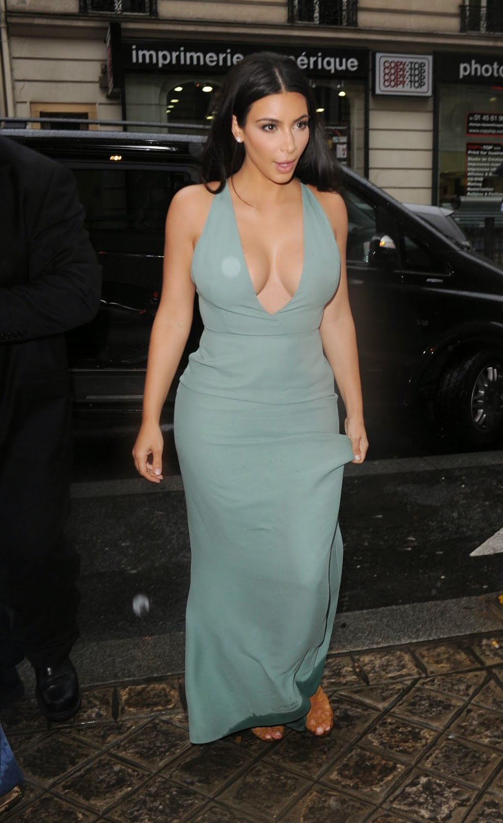 Kim Kardashian displays cleavage in a low cut gown at the Fall 2014 ...