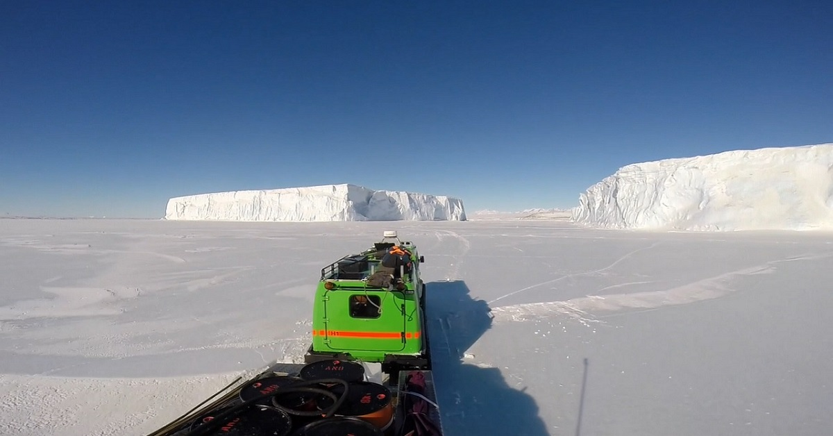 Hagglunds driving on sea ice between massive icebergs in Antarctica