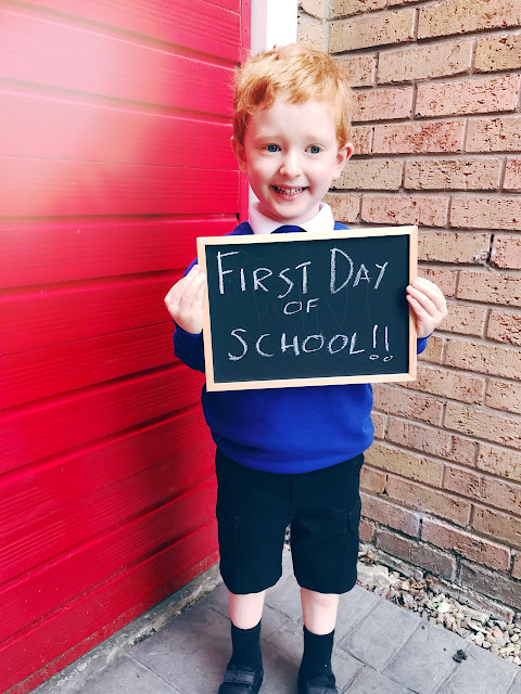 Little boy dressed in a school uniform holding up a sign that says first day of school