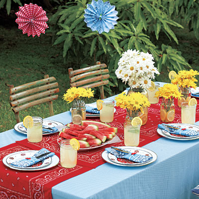 This outdoor Memorial Day picnic area features bandanna napkins and a table runner.