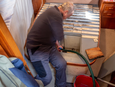 Photo of Phil pumping out the water from the bilges under our bed