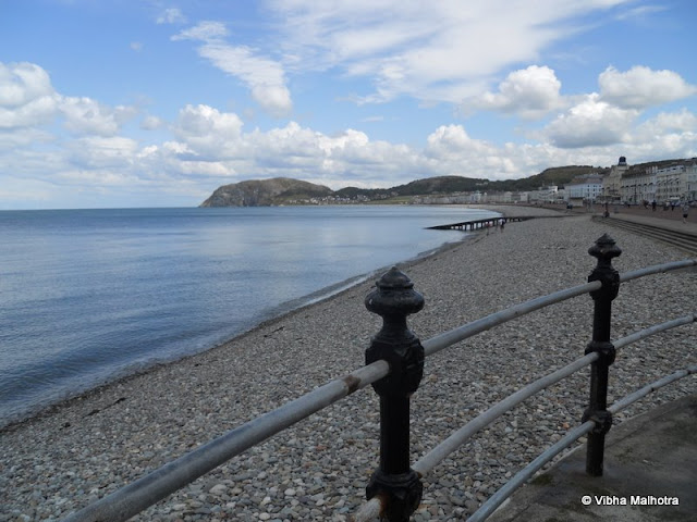 Last year in June, I got the opportunity to visit the North of Wales in the UK with my friends on a coach trip. We were put in a pretty rugged hotel in the sleepy town of Llandudno (don't ask me how that is pronounced) and we were to go out to different places on our coach for the next three days. The town of Llandudno overlooked the comparatively serene Irish sea and was quite a sweet place to hang out in actually. Here are some sights from the delightful town.Here's the quiet beach on the North Shore. This was just a few minutes walk away from our hotel and we religiously came here every evening to walk on the beach. The water was blue, unlike the grey North Sea and it was quite serene when compared to the Pacific Ocean. There were some really pretty windmills out in the sea. I think the wind velocity was enough to generate a lot of power. And they made for pretty sight-seeing as well. A church on the street. The town was sleepy and quiet and a very chilled out place to stay in. Whenever I retire, I would love to stay at a place like this. Caught this cute little windmill lamp in front of a restaurant. Notice how there's no dust or dirt. It is mostly because it rains so much in the area. Grumpy's sweet shop. Need I say more? Pretty little pebbly beach with mild waves. The tide is not too high and cotton clouds dot the sky. A perfect day to be out. Days were pretty long back then. I think this was around 8 PM. This is the other side of the beach. In the distance is the pier, a wooden walkway into the sea. It had several shops selling trinkets, shells, magnets and seafood. The beach was quite long and we didn't manage to walk the entire length during our stay there. Colourful pebbles beneath the water. This beach was different from any I had seen before. I was looking for shells while my friend Kelsey collected sea-glass. People canoeing on the sea. I somehow can never trust myself on such a tiny boat on a vast body of water. Hannah in a meditative mood down the pier. The sea looks deceptively calm. However, the waters were full of jellyfish. We saw several divers and swimmers come out of the sea with their legs bleeding.  A memorial on The Parade that runs parallel to the North Shore. The entire area was shaped like a C and was bordered by candy-coloured houses. A very charming place to be indeed. A colourful little train that runs along The Parade. It is very popular with children and the grown-ups alike On the whole, North of Wales was a whole new level or prettiness. Watch out for the next post. It'll definitely fascinate you. :)