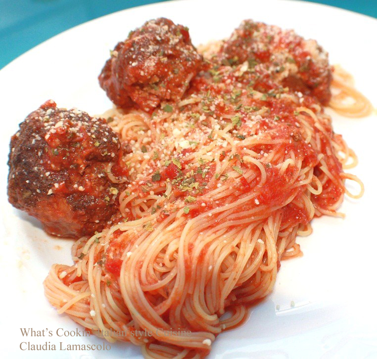this is a homemade thick tomato Italian sauce over spaghetti,  with sausage and meatballs with pork spare ribs
