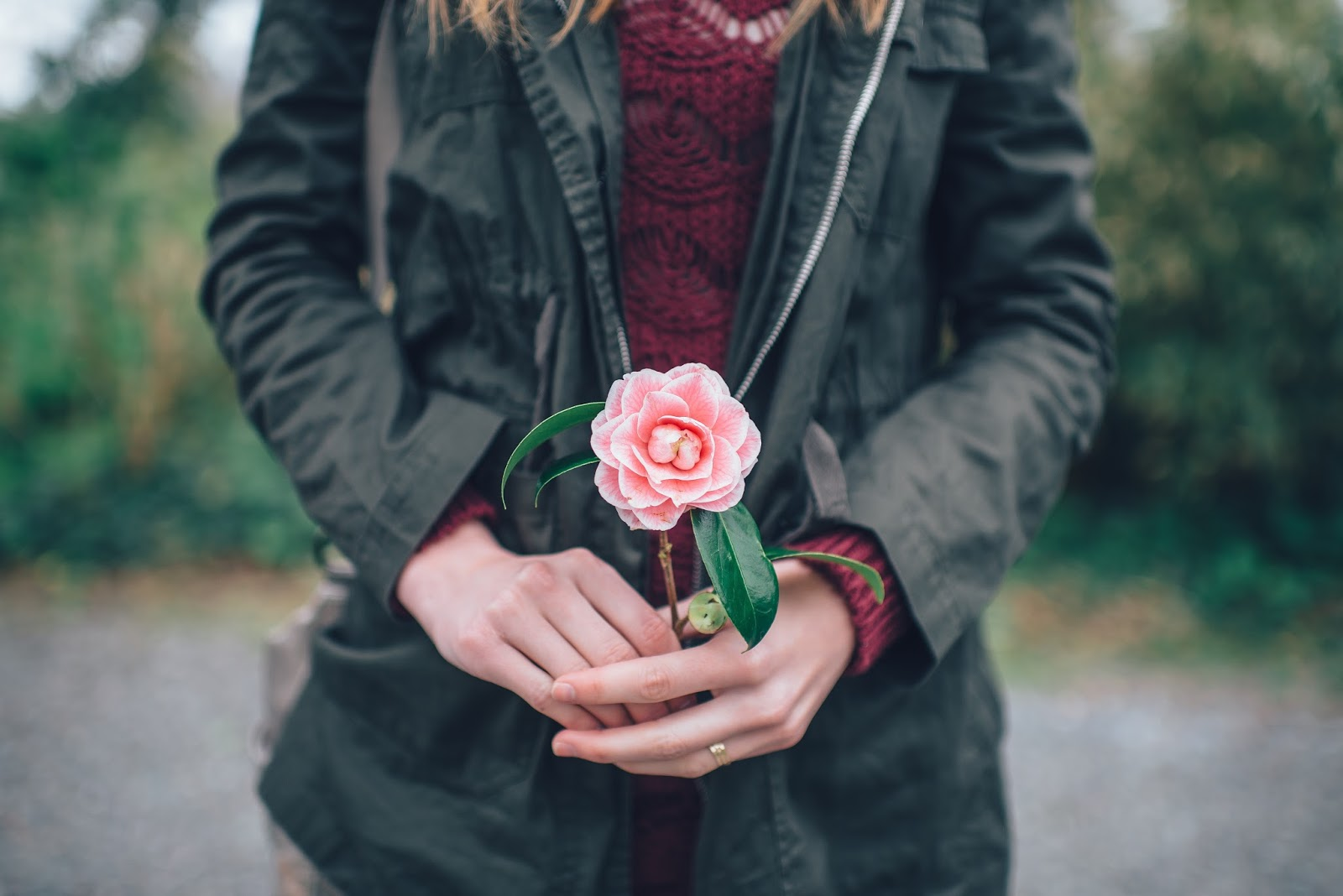 woman in black leather jacket holding pink rose