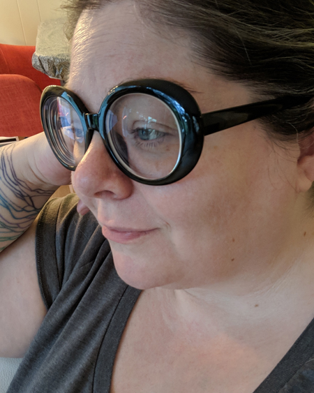 image of me in profile, from the shoulders up, with my hair up and wearing a grey t-shirt and large black-framed glasses, in the lenses of which is reflecting the sky through a window