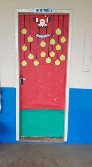 Decoração de porta com Papai Noel segurando plaquinha e bolinhas natalinas onde serão colocadas fotos das crianças.